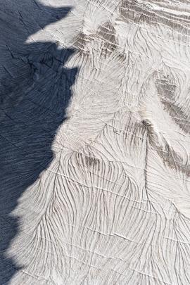La cresta di una montagna proietta la sua ombra su un ghiacciaio in alta quota. Georgia